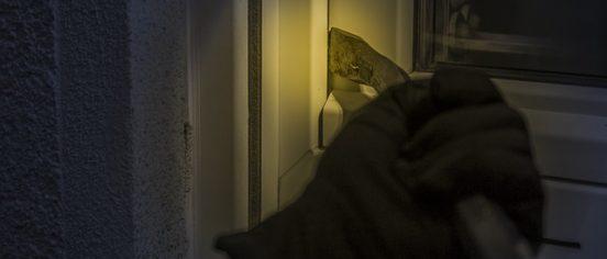 Burglar with crowbar breaking in